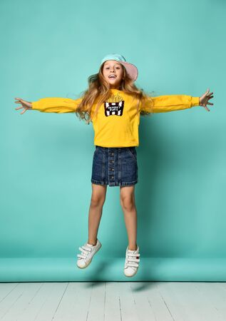 Funny teenage girl in a baseball cap and a yellow hoodie and a denim miniskirt posing in full growth on a blue background. Girl jumping