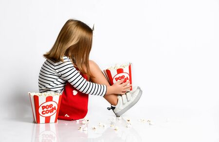 Side view of a little cute girl sitting on the floor with two buckets of popcorn and sad sprinkled popcourt on the floor