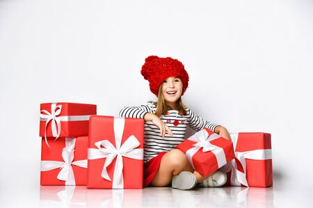 Portrait of a joyful cute little girl in a red hat sitting in a pile of gift boxes, enjoys the holiday on a light isolated background.