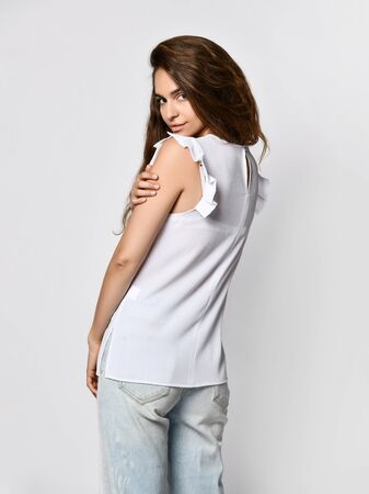 Fashion model wearing ripped boyfriend jeans, white blouse shirt. Fashion urban outfit. Casual everyday clothing style. Stockfoto - 134275419