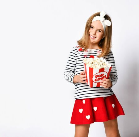 Young little girl in red skirt holding bucket with popcorn on grey background