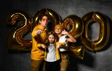 Happy young friends children with golden balloons 2020 on dark concrete background. New Year celebration. Two sisters and an older brother, modernly dressed teenage children. Stockfoto
