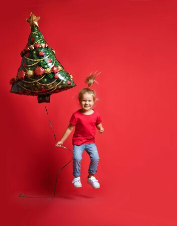 toddler girl in a red T-shirt, blue jeans, bounces with joy holding a Christmas tree balloon on a red background with free copy space. New Year and Christmas with holiday concept Stockfoto - 134594535