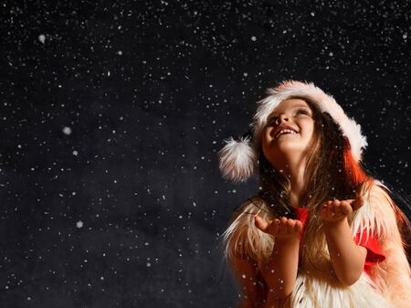 Little cute girl in a santa hat and white fur vest, catches snowflakes on a dark background. Waiting for a miracle on Christmas Eve Stockfoto