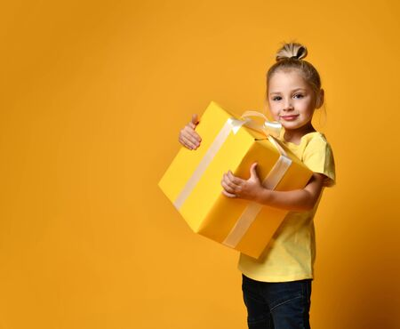 Joyful little girl with gift box in t0shirt and jeans on yellow background
