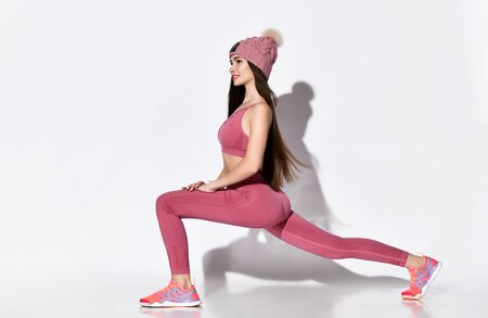 Profile photo of an energetic brunette athlete of the 20s in a tracksuit with pink tops and legends, a warm knitted hat with a pompom, lunges and kneading legs on a light background