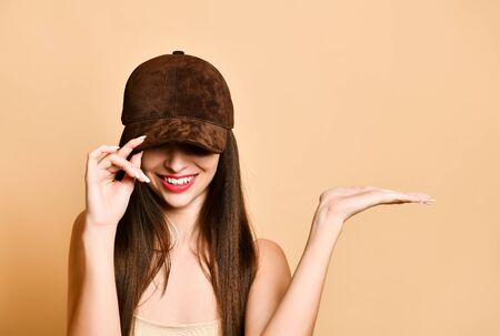 brunette in a brown suede baseball cap hides her face under a cap and shows something with her hand