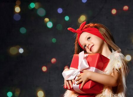 Dreamy little girl in a fur sleeveless jacket and a red bandage on her hair holds a Christmas present to herself. She waits for Christmas and holiday. Stockfoto