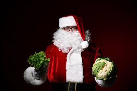 Jolly Santa Claus holds in one hand a bunch of lettuce in another swing of cauliflower. The choice. Enjoy a healthy Christmas dinner. Healthy Christmas Recipes. Christmas diet.