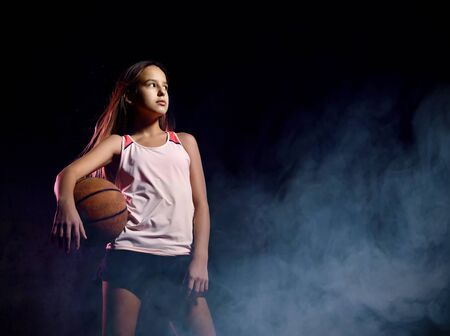 Portrait of young female basketball player passing the ball. Beautiful caucasian woman in sportswear playing basketball on grey background with smoke effect