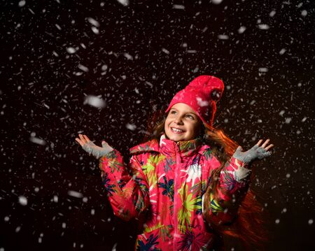 Young beautiful happy little girl on a dark background, looks up catches snowflakes, wearing a stylish winter jacket, hat, gloves. Empty copy space for text.