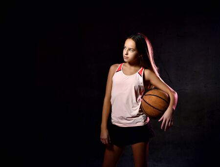 Portrait of female basketball player in uniform holding ball while looking away space for ad