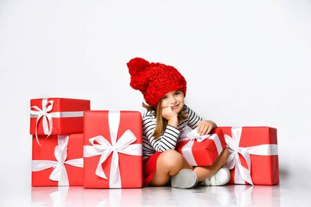 Portrait of a bored cute little girl in a red hat sitting in a pile of gift boxes, after shopping or after the holiday.