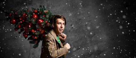 Teenager man carrying a Christmas tree. Young man in a jacket carrying a Christmas tree decorated with red Christmas balls. Merry guy holds a Christmas tree on his shoulders. holidays.