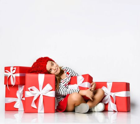 cute baby in a red hat sits on the floor, around there are gift red gift boxes with white ribbons and dreams of something. on a light background. Stockfoto