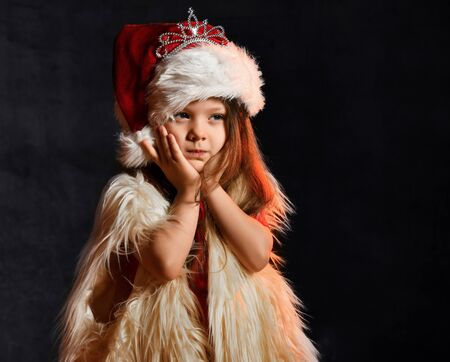 Little girl in santa hat and fur yolk posing on a dark background. Little kid with santa look. Stockfoto