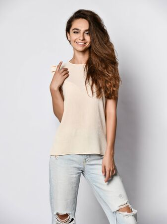 Fashion model wearing ripped boyfriend jeans, white blouse shirt. Fashion urban outfit. Casual everyday clothing style. Stockfoto - 134594756