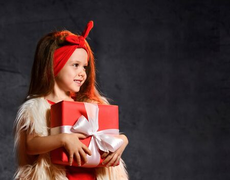 Happy little smiling girl with christmas gift box and looking away