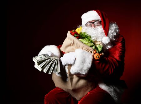 Jolly Santa Claus is holding a big bag full of fruits and vegetables. Holds a carrot in his teeth like a cigar. Enjoy a healthy Christmas dinner. Healthy Christmas Recipes. Christmas diet.