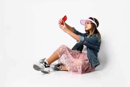Attractive teenager girl takes a selfie on her mobile phone, sitting on the floor in the studio in a stylish cap and denim jacket