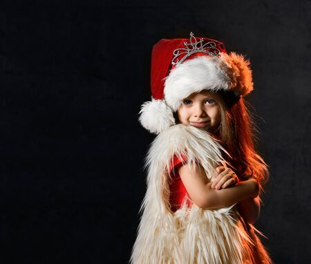 Little girl in santa hat with crown decoration and a fur yolk posing on a dark background. Little kid with santa look. Stockfoto