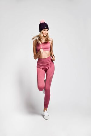 beautiful sexy blonde with a perfect athletic slim figure, leads a healthy lifestyle - went for a morning run in comfortable pink sportswear and a hat with pompons
