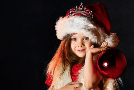 Little girl in a santa hat and a fur yolk holds a red gift ball, Christmas tree toy. Little kid with santa look. Christmas present. New Years gift. Stockfoto