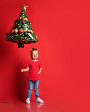 Happy toddler girl in a red T-shirt, blue jeans holding a Christmas tree balloon on a red background with free copy space. New Year and Christmas with holiday concept