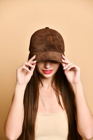 brunette in a brown suede baseball cap holds her visor cap with her hands, hiding her face underneath Imagens
