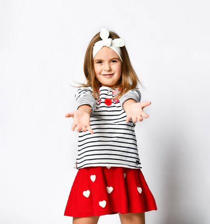 Portrait of a friendly caring little girl with a happy smile, pulling her hands to the camera, inviting to hug, joyfully standing on a light background Stock fotó