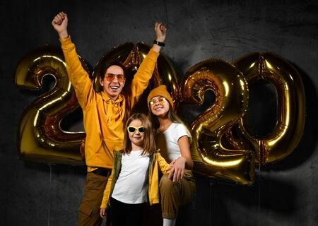 Happy young friends children with golden balloons 2020 on dark concrete background. New Year celebration. Two sisters and an older brother, modernly dressed teenage children. Фото со стока