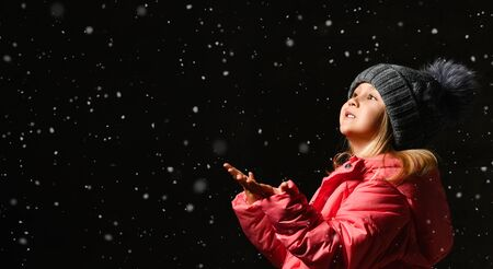 Little girl catches snowflakes stretching out her hands forward. A child enjoys playing outdoors. Merry Christmas and happy holidays. Portrait of a kid on a dark background. side view