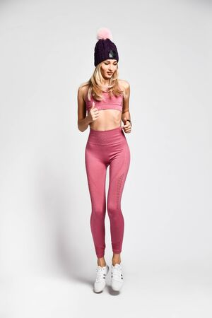 Beautiful sexy blonde with a perfect athletic slim figure, leads a healthy lifestyle, wears comfortable pink clothes in the style of sports. Warm hat with pompons Foto de archivo