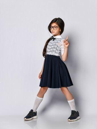 colegiala en forma de blusa blanca, lleva gafas. El alumno muestra un dedo hacia arriba, preste atención a lo que necesita saber. El uniforme escolar de ropa para niños prepara sus conocimientos para la lección.