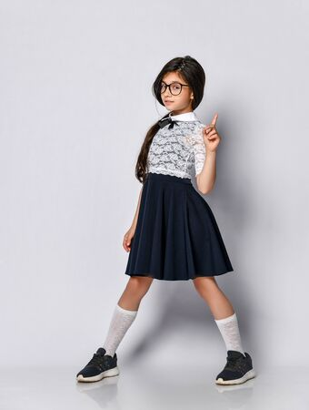 school girl in the form of a white blouse, wears glasses. The student shows a finger up, pay attention to what you need to know . Children's clothing school uniform prepares their knowledge for the lesson.