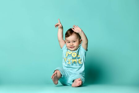 Little cute boys baby sits on the floor in the studio in a summer cotton suit in shorts and a t-shirt, on a turquoise background. isolated