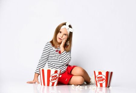 baby in confusion. I can not master so much popcorn. Sitting on the floor in the back of her mind with two buckets of popcorn