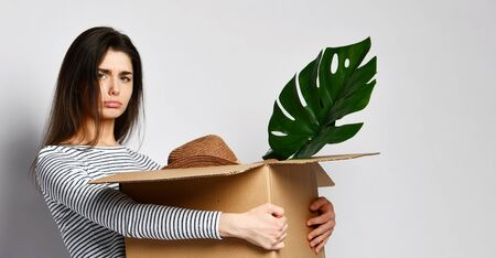 dolorous young attractive brunette girl holds a cardboard box full of things - plant, hat and others. She is dressed in jeans and a casual jersey. Concept relocation fees