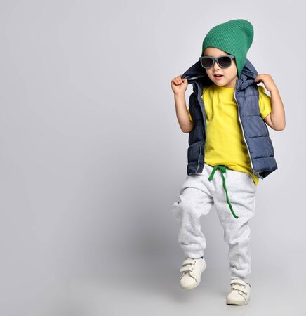 Stylish cheerful little boy 4 years old in sweatpants, a green hat, glasses and a down vest has fun on a light background