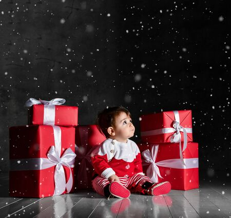 Little baby santa assistant in the entourage of the gift looks surprised at the top. It is snowfall