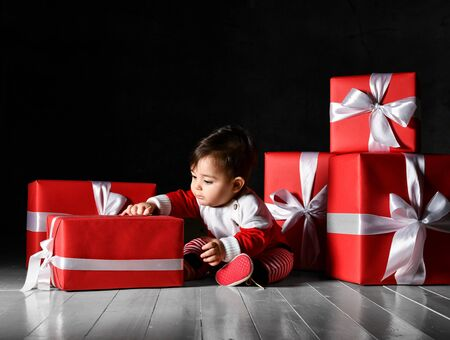 Infant boy sitting in a red sweater like a Santa suit and gift box for Christmas, plays on a dark background