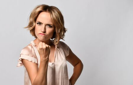 Angry beautiful young woman shows a fist to the camera, threatens someone, annoyingly purses her lower lip, wrinkling her nose and grinning teeth, dressed in casual clothes, isolated on a light background