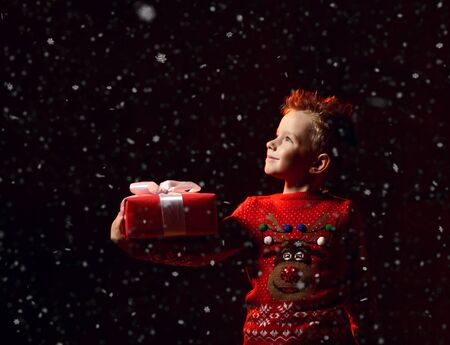 Little happy boy in a red sweater with an image of a rudolph deer holds a gift from Santa, snowfall