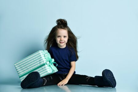 Small smiling girl in t-shirt, leather leggins and dark blue ugg boots sitting on floor and leaning on big present box over blue wall background. Stock fotó