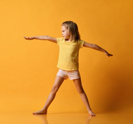 Smiling girls practicing yoga, standing in war pose side view, working out wearing sportswear, t-shirts, pants, yellow studio background