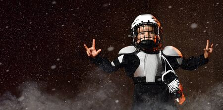 Positive boy in hockey uniform and protective helmet with hockey skates standing and showing little finger and forefinger, forward good sign dark background with snow and smoke
