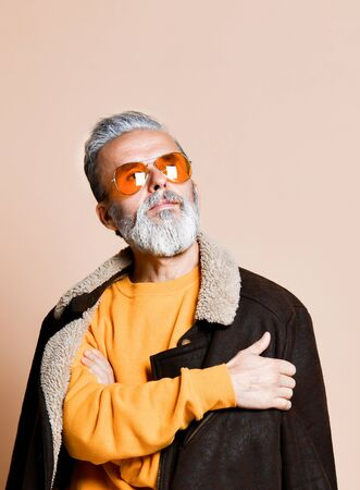 Portrait of senior stylish rich man with a beard and mustache in a leather coat, a stern look away through yellow modern glasses, the studio on a beige background