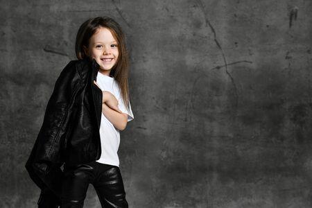 Pequeña niña linda sonriente en ropa casual de estilo estrella de rock blanco y negro y zapatillas blancas de pie sobre fondo de hormigón gris en estudio fotográfico. Concepto de ropa de niños con estilo Foto de archivo