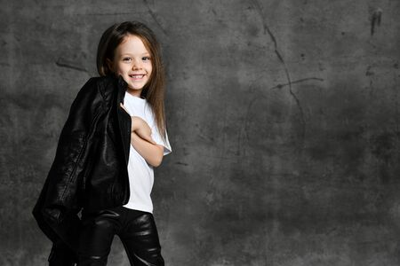 Small smiling cute girl in black and white rock star style casual clothing and white sneakers standing over grey concrete background in photo studio. Stylish children clothing concept Stock Photo