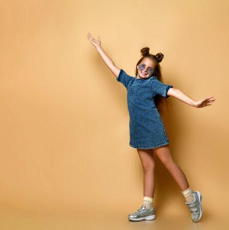 Vue latérale du profil photo d'une jeune femme avec une coupe de cheveux moderne, une robe en jean décontractée regarde la caméra avec un grand sourire blanc montre les doigts